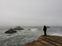 Man on a ledge overlooking the Pacific Ocean, Lands End, San Francisco, CA
